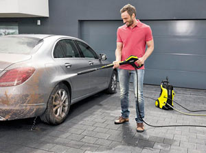 Smiling men washes his car with cold water pressure washer